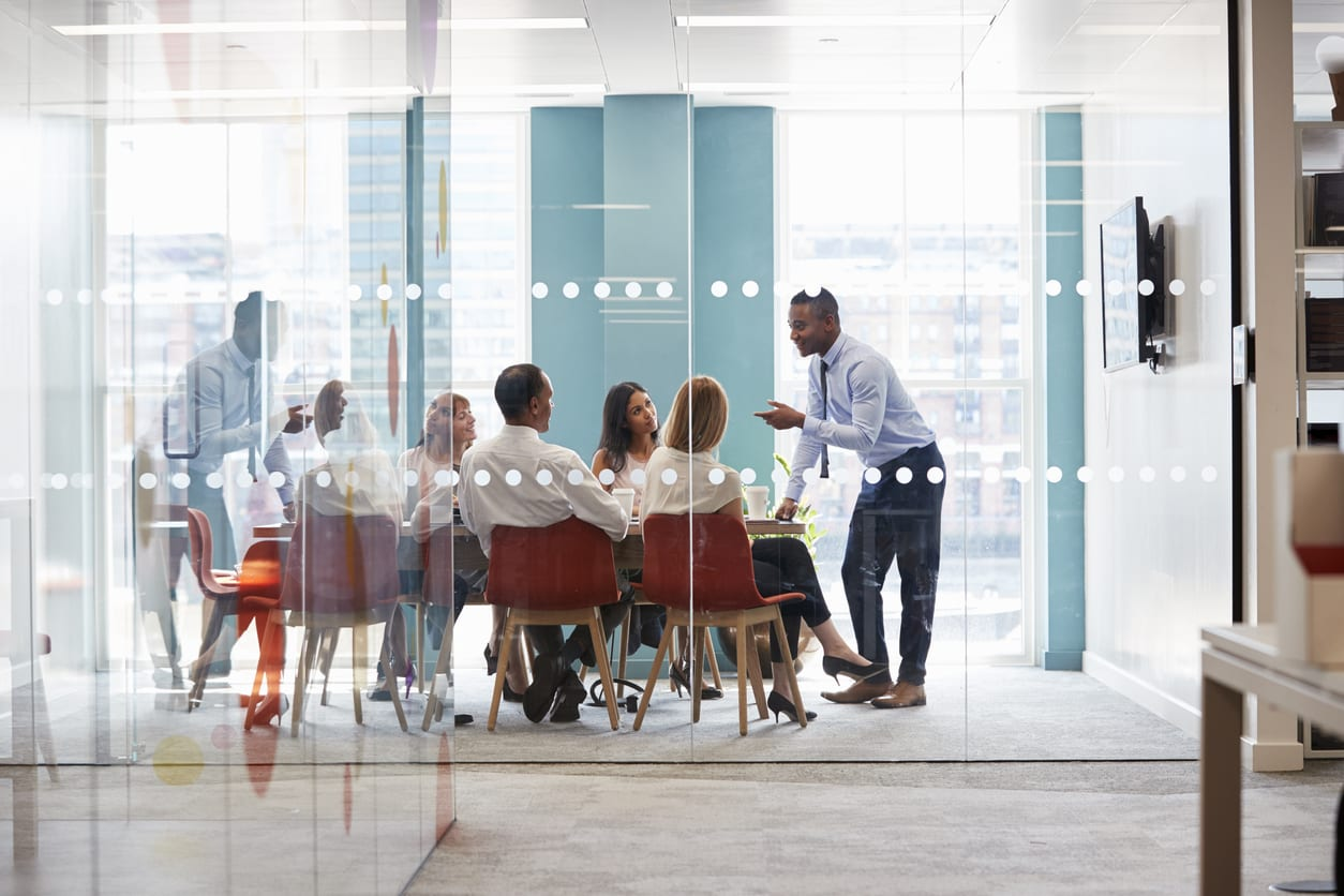 Colleagues chat informally in boardroom