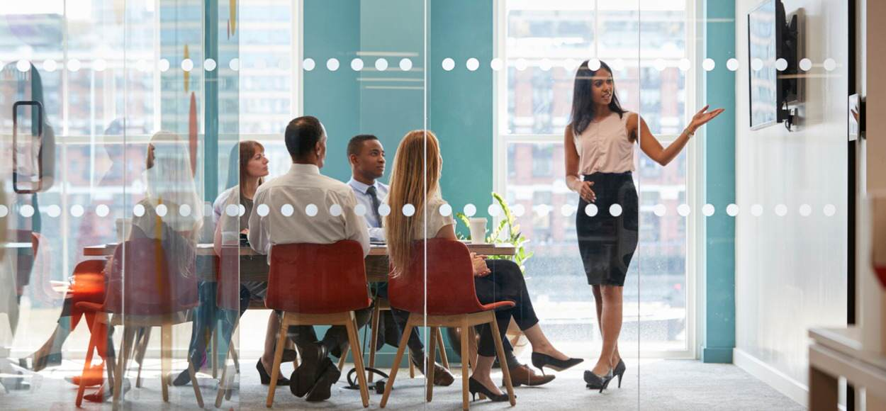 Female boss carries out presentation in front of colleagues in office
